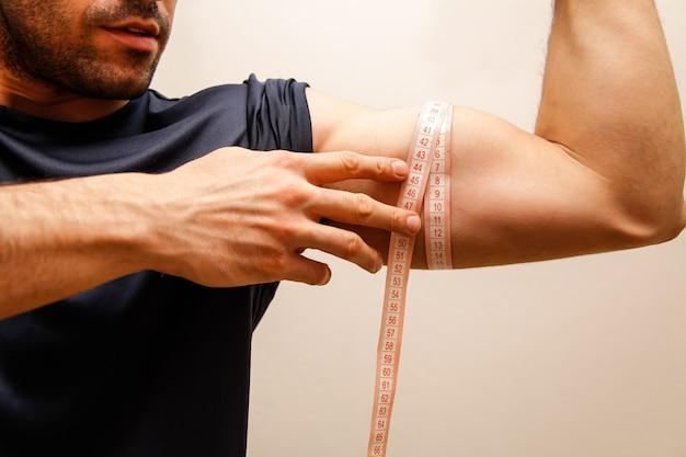 Mięśniowy mężczyzna mierzy jego bicepsy z pomiarową taśmą