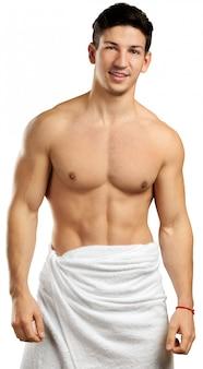 Mięśniowy mężczyzna odizolowywający na bielu