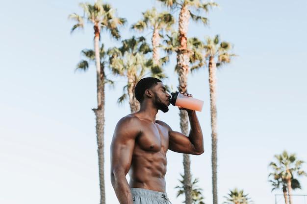 Mięśniowy mężczyzna pije proteinowego potrząśnięcie