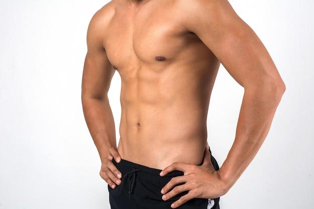 Mięśniowy mężczyzna pokazuje sześć paczek abs odizolowywających na białym tle.