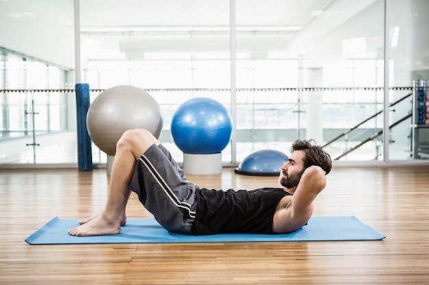 Mięśniowy mężczyzna robi brzusznemu na macie w studiu