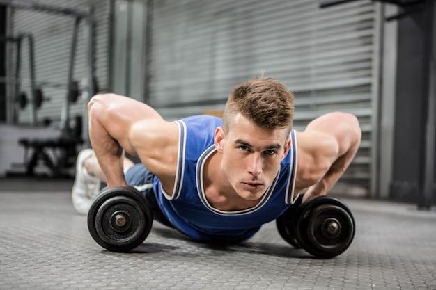Mięśniowy mężczyzna robi pcha up z dumbbells przy crossfit gym