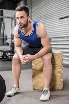 Mięśniowy mężczyzna siedzi na drewnianym bloku przy gym crossfit