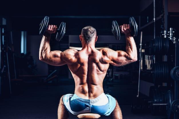 Mięśniowy mężczyzna trenuje jego ramiona z dumbbells w gym