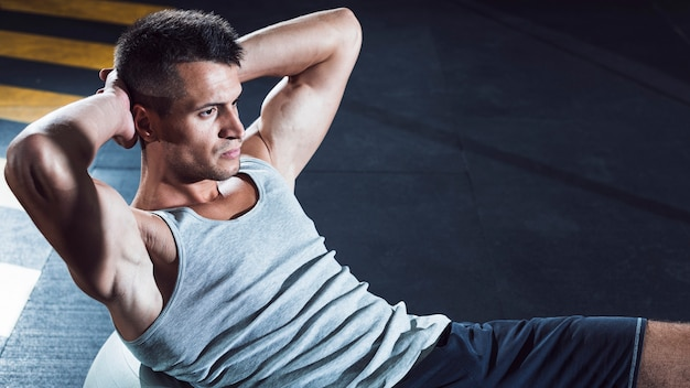 Mięśniowy młody człowiek ćwiczy w sprawność fizyczna klubie