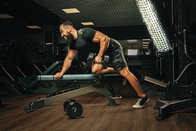 Mięśniowy młody człowiek podnosi ciężary w ciemnym gym
