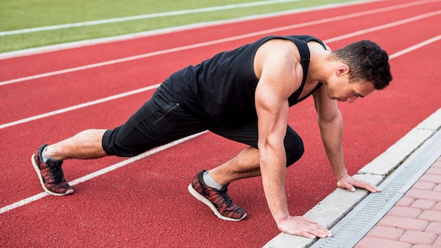 Mięśniowy młody człowiek robi fitness pushup na czerwonym bieżni
