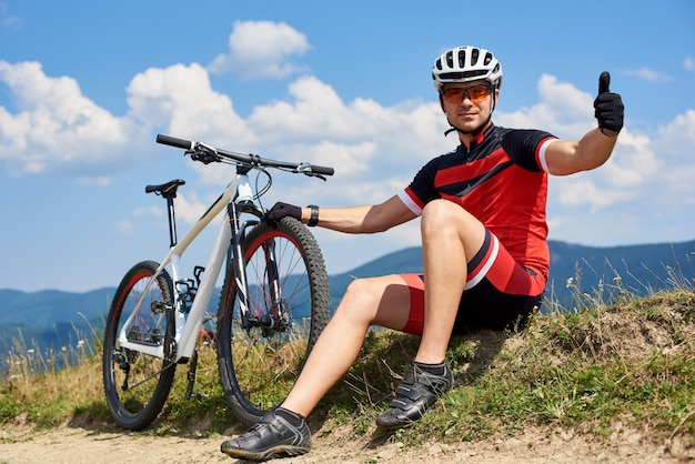 Mięśniowy sportowa bicyclist siedzi blisko jego roweru górskiego na trawiastym poboczu, pokazuje aprobaty, odpoczywa po jechać bicykl w pogodnym letnim dniu. koncepcja sportu na świeżym powietrzu