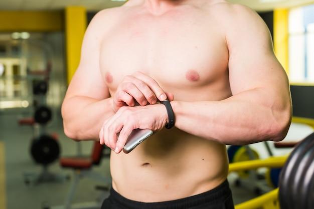 Mięśniowy sportowiec sprawdza program treningowy na aplikacji na smartfony po doskonałym crossfit w siłowni