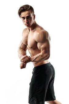 Mięśniowy super pozioma przystojny mężczyzna pozuje na białym tle