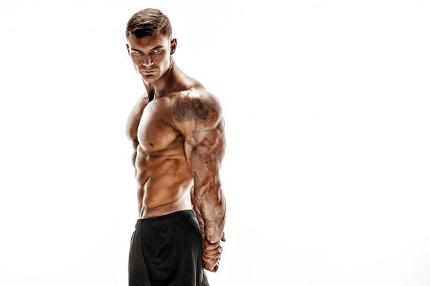Mięśniowy super wysokiego poziomu przystojny mężczyzna pozuje na białej scenie