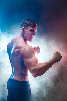 Mięśniowy wojownik uderza pięścią w dym. kolor tła.