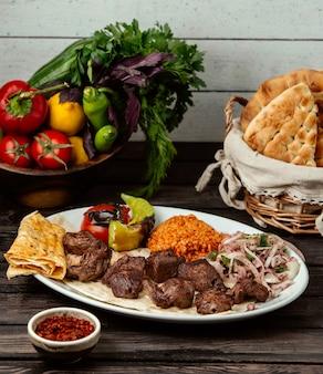 Mięsny bulgur i cebula z sumakiem na drewnianym stole