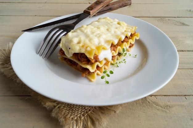 Mięsny lasagna na drewnianym tle.
