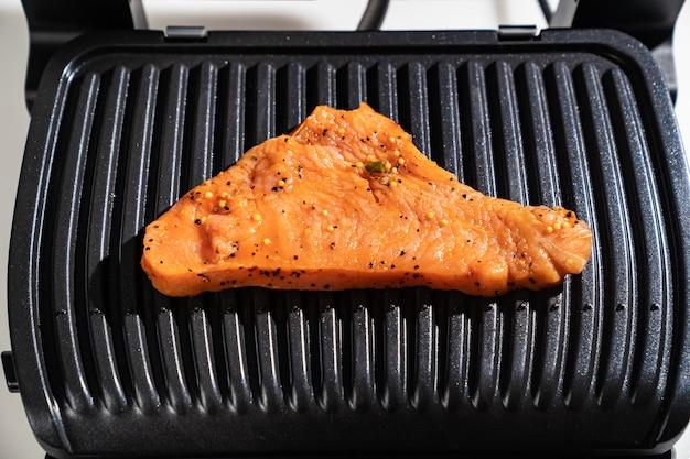 Mięso gotuje się na grillu elektrycznym. urządzenie do gotowania w życiu codziennym. wykonany ze stali nierdzewnej, ze specjalną powłoką zapobiegającą przywieraniu. zdrowe jedzenie. jedzenie bez oleju i tłuszczu.