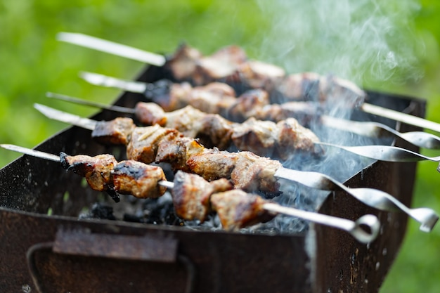 Mięso grillowe na szaszłykach. gotowanie szaszłyka na mangalu w naturze. szaszłyk z grilla gotowanie na metalowym szpikulcu. domowy piknik