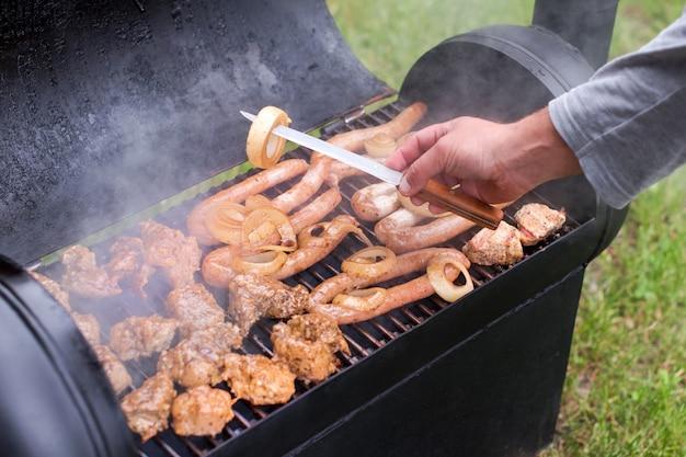Mięso i kiełbaski na grillu na świeżym powietrzu na zielonym trawniku. mężczyzna gotuje