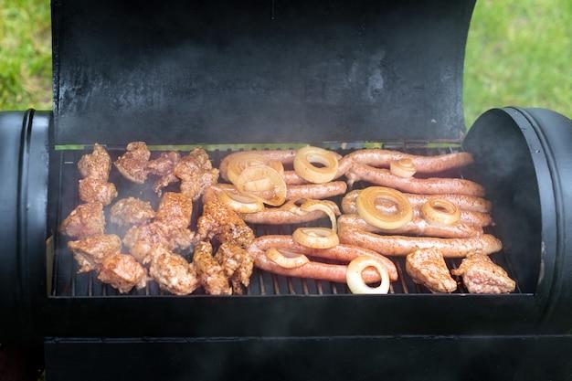 Mięso i kiełbaski na grillu na świeżym powietrzu na zielonym trawniku.