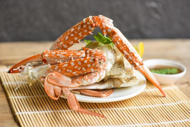 Mięso kraba - gotowane pazury i nogi kraba na białym talerzu i sos z owoców morza na stole, niebieski krab pływający