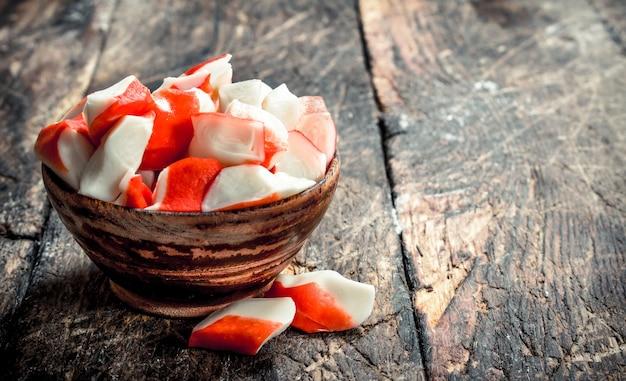 Mięso kraba w misce. na drewnianym tle.