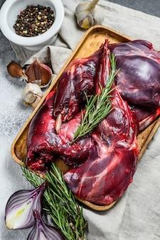 Mięso królika surowy świeży rolny królik na drewnianym stole z warzywami i pikantność.