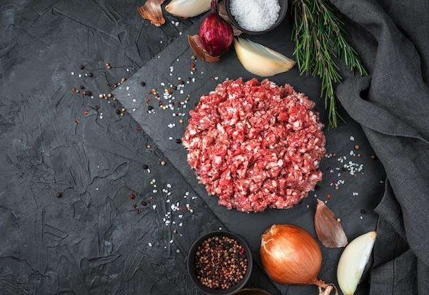 Mięso mielone i dodatkowe składniki na czarnym tle. widok z góry, z miejscem do skopiowania. pojęcie gotowania.