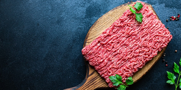 Mięso mielone mięso wieprzowe lub wołowe na drewnianym stole, widok z góry