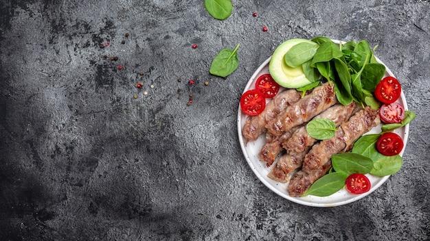 Mięso mielone owinięte bekonem ze szpinakiem, awokado i pomidorkami koktajlowymi, zdrowe tłuszcze, czyste jedzenie na odchudzanie. format długiego banera. widok z góry.