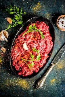 Mięso mielone z przyprawami i świeże zioła na ciemnym stole, copyspace widok z góry