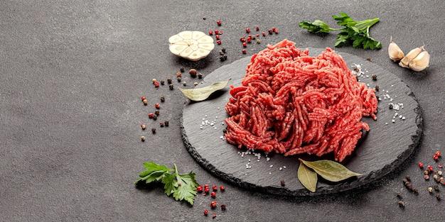 Mięso mielone z przyprawami na desce łupkowej