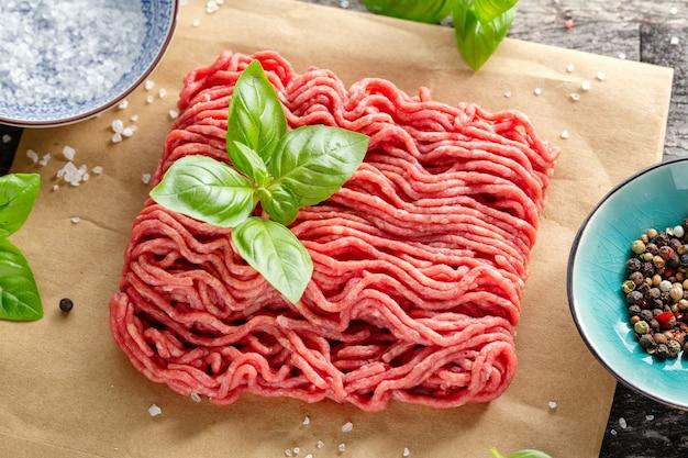 Mięso mielone z przyprawami na papierze na stole. zbliżenie