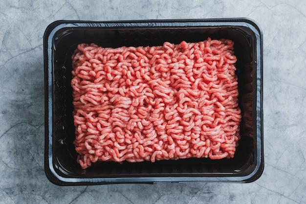 Mięso mielone z przyprawami w pudełku na stole. zbliżenie
