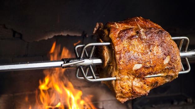 Mięso na rożnie w piekarniku. schab z grilla w otwartym płomieniu. copyspace
