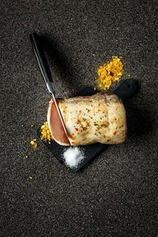 Mięso peklowane na sucho z przyprawami i solą, nóż kroi plasterek, na ciemnoszarej powierzchni