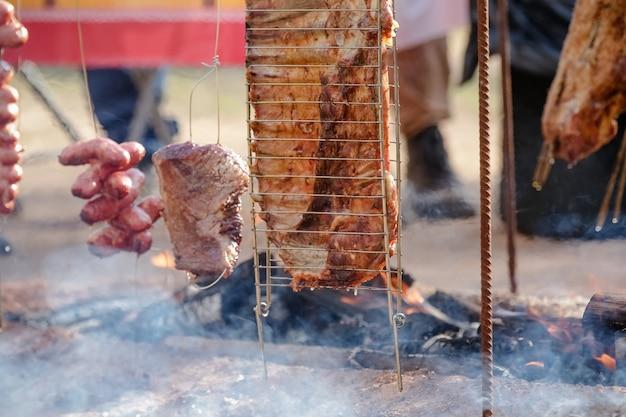 Mięso pieczone i krojone na stole i ognisku z drewnem opałowym w stylu gaucho
