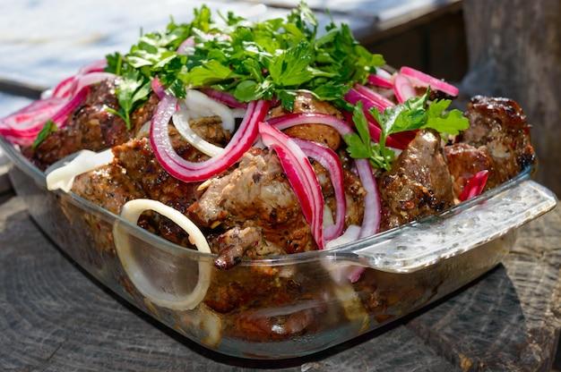 Mięso pieczone na szaszłykach na otwartym ogniu z kiszoną cebulą i zieleniną na tle przyrody. szaszłyk. piknik