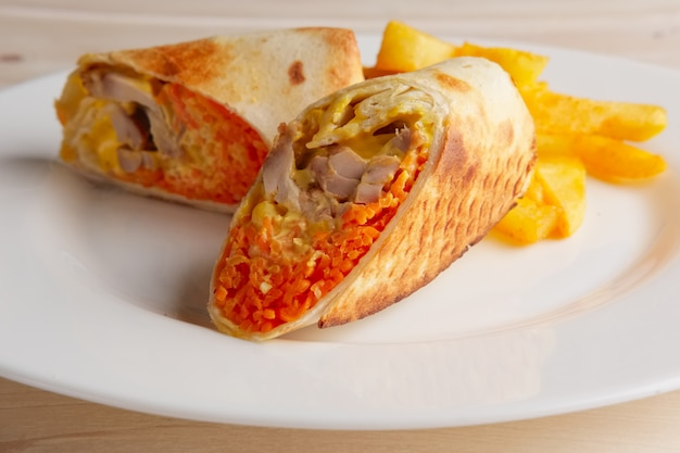 Mięso, pikantna marchewka, kapusta i ser zwinięte w cienkim pieczywie pitta