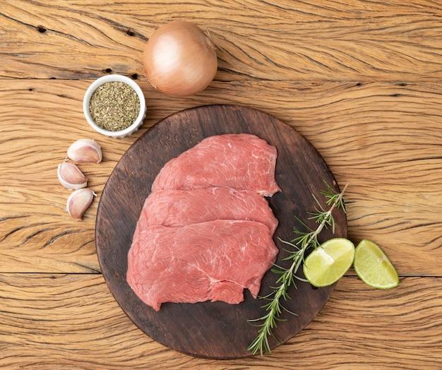 Mięso rumsztyk na desce z przyprawami.