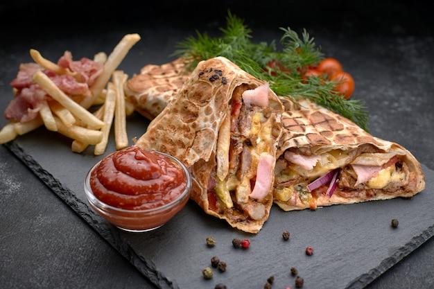 Mięso shawarma z boczkiem, ziemniakami, ziołami, pomidorami i sosem, na czarnym tle