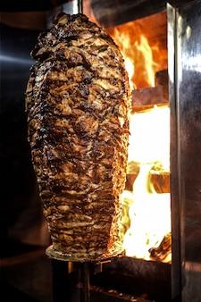 Mięso shawarma z węgla drzewnego. zbliżenie mięso z kurczaka zebrane na pionowym szpikulcu i grillowane na węglu drzewnym.