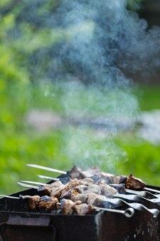 Mięso smaży się na szaszłykach na mangalu. mięso grillowane na szaszłykach w dymie. gotowanie z grilla kebab w wiejskim domu. skopiuj miejsce