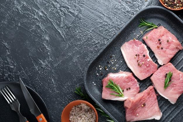 Mięso. surowe kawałki wieprzowiny z rozmarynem i pieprzem na czarno