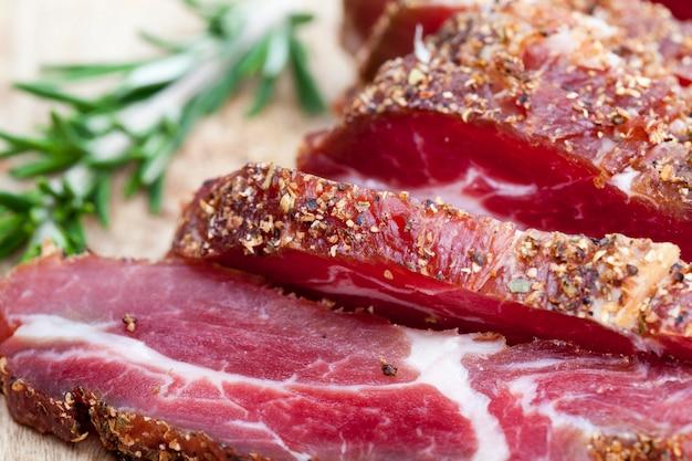 Mięso wieprzowe marynowane, wędliny wieprzowe ze smalcem pokrojone na stole