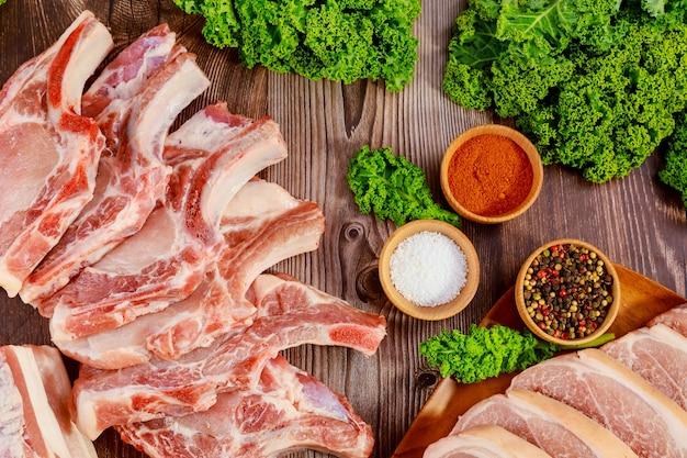 Mięso wieprzowe pokrojone w kostkę i przyprawy na drewnianym stole..