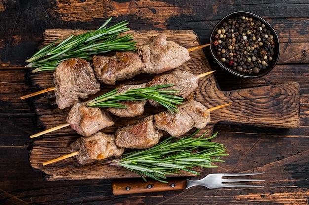 Mięso wieprzowe szaszłyk na szaszłykach z ziołami na drewnianej desce. ciemne drewniane tło. widok z góry.