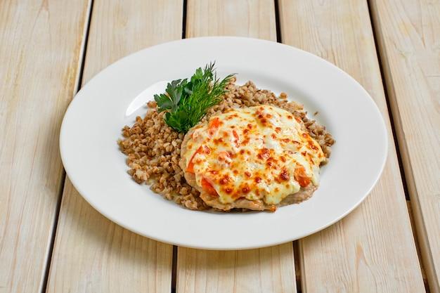 Mięso wieprzowe zapiekane z serem i pomidorem podawane z kaszą gryczaną