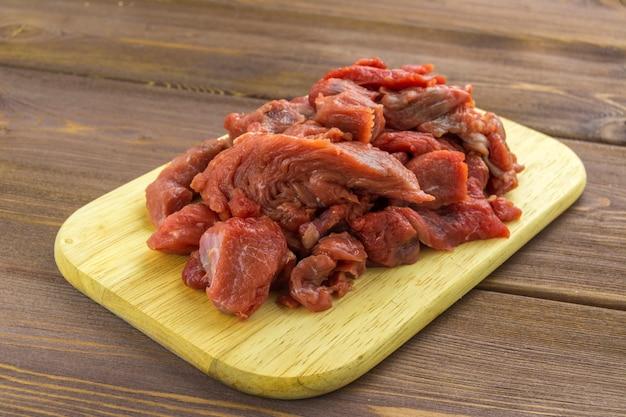 Mięso wołowe pocięte na kawałki leży na desce