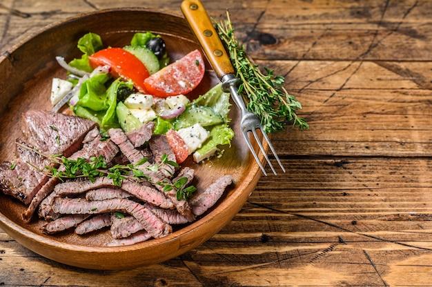 Mięso wołowe z grilla kotlet rumsztyk na drewnianym talerzu z sałatką jarzynową. drewniane tła. widok z góry. skopiuj miejsce.