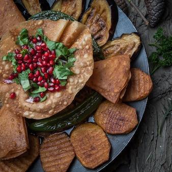 Mięso z bliska z pieczonymi ziemniakami, bakłażanem, pomidorem, pieprzem i ozdobione granatem na drewnianej korze