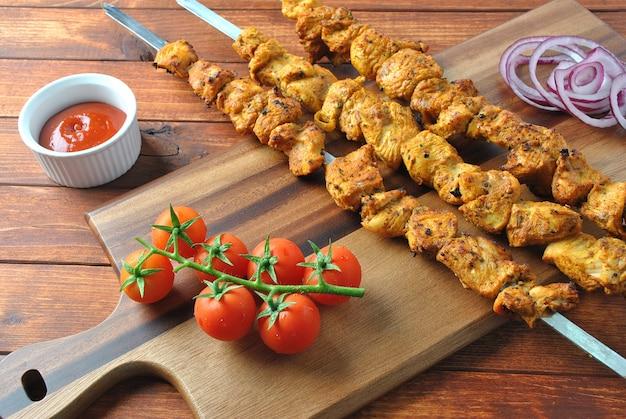 Mięso z grilla. kebab z kurczaka. szaszłyk z kurczaka z warzywami na podłoże drewniane. styl rustykalny. widok z góry